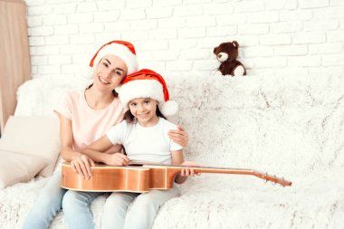 Mom and daughter are resting at home and playing the guitar.