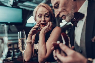 Businesswoman and Businessman . Old Business People .Successful Old People. Relax together. Romantic Meeting, Rich People. Couple Resting in Restaurant. Man gives ring to woman. woman thrilled
