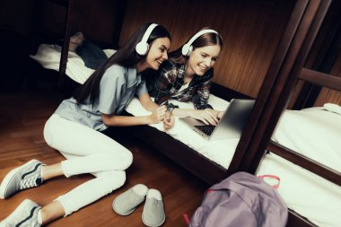 Hostel for Young People. Best Friends Traveling. Small Room in Hostel. spend time Together. bunk beds in room. smiling Woman. looking at laptop . girls on bed. listen to music. sitting on floor