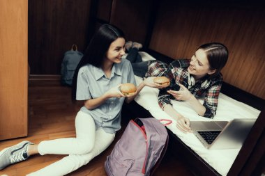 Hostel for Young People. Best Friends Traveling. Small Room in Hostel. spend time Together. bunk beds in room. smiling Woman. looking at laptop . girls on bed. sitting on floor. eat together