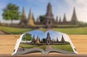 Kreativität Reiseführer, offenes Buch auf Holztisch mit verschwommenem Naturhintergrund, Szene Ayutthaya historischer Park.