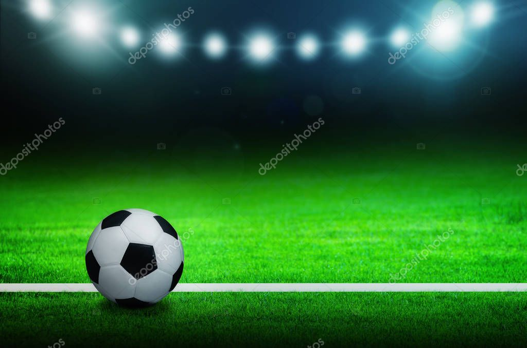 Ball, Football, Soccer ball on green stadium, arena in night illuminated bright spotlights.