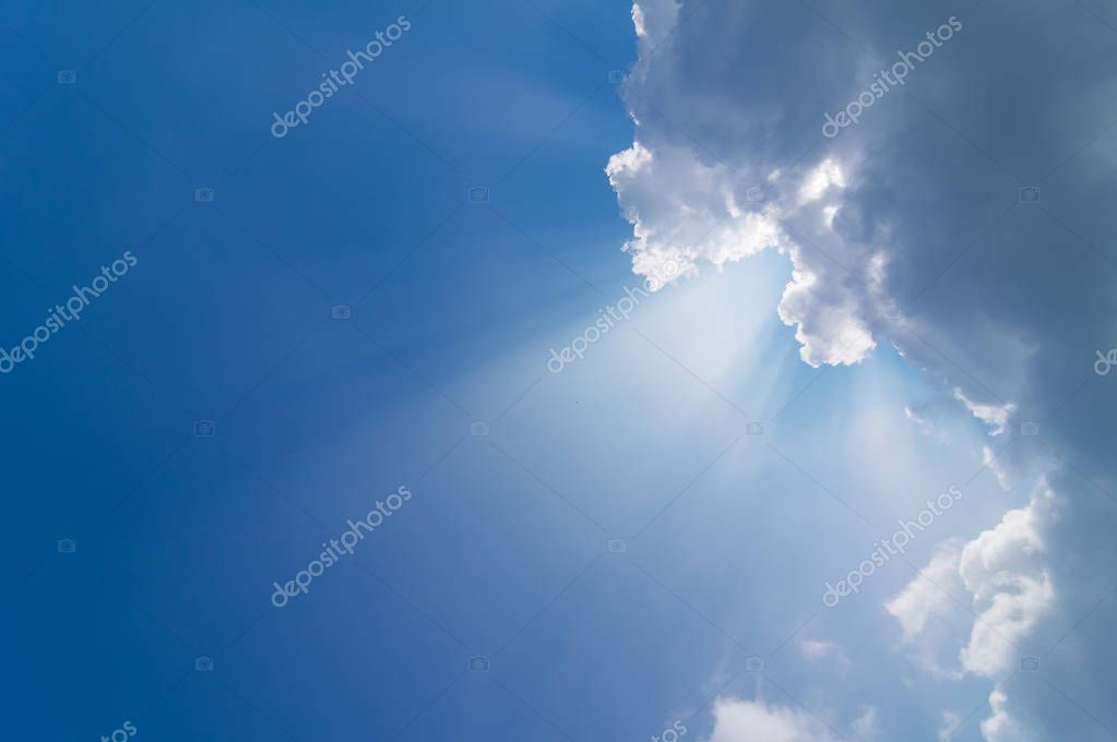 Beautiful sun rays from behind clouds on blue sky.