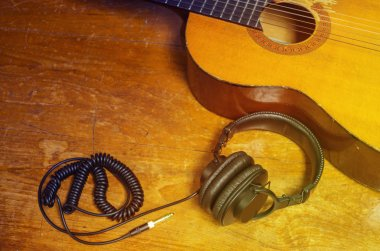 Acoustic guitar and headphone on old wooden table.
