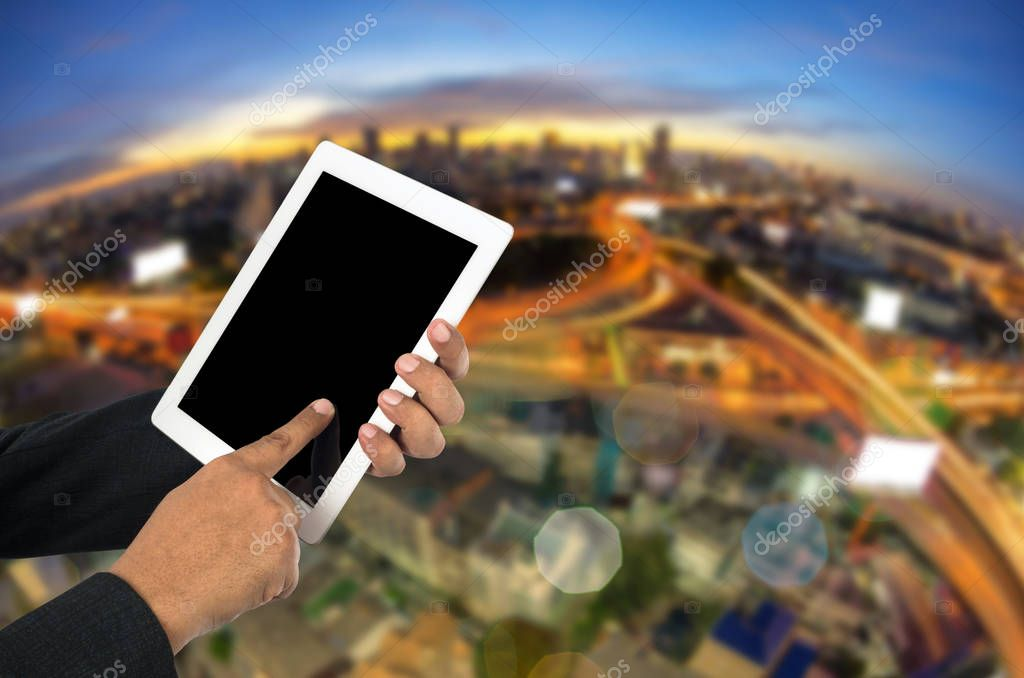 Businessman using tablet pc and city landscape at background.