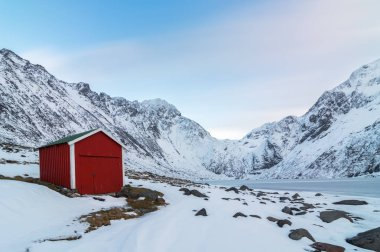 Red wooden cabin in winter on the island, Norwegian style.