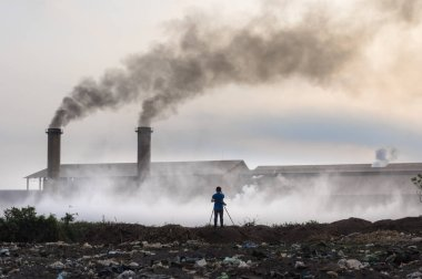 Air pollution with black smoke from chimneys and industrial waste.