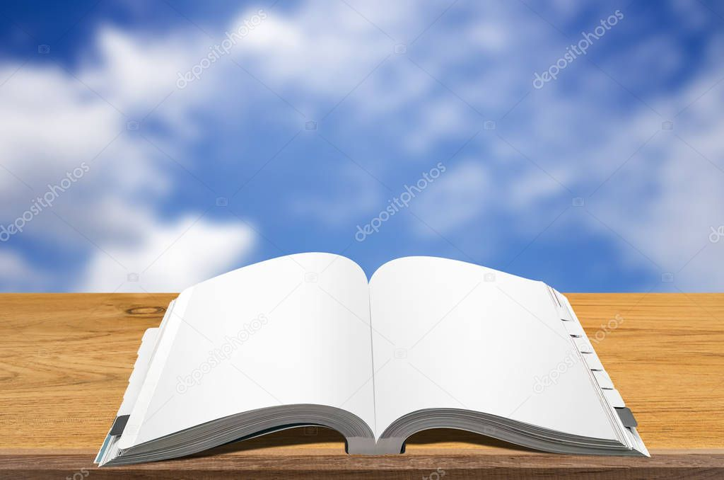 Open book on wooden table with blurred sky background.