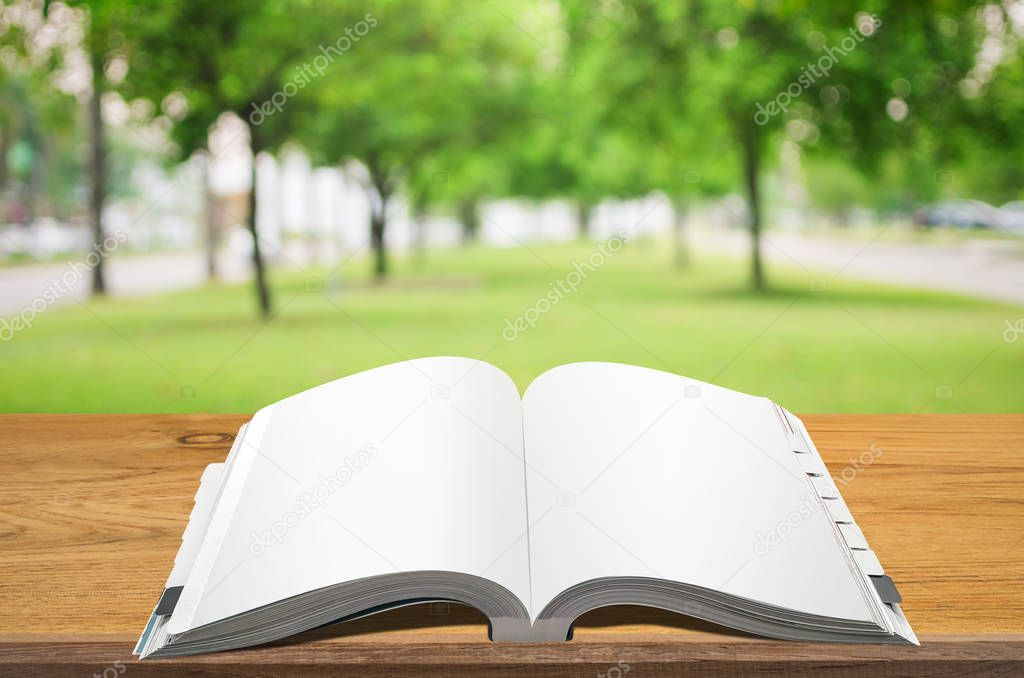 Open book on wooden table with abstract blurred light background.