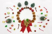 Photo Christmas background with gift box, fir tree, conifer cone, christmas ball, christmas wreath, New Years interior and holiday decorations on white from above. Flat lay style.