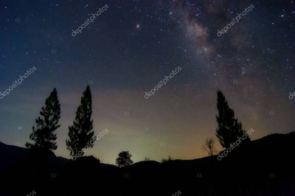 Milky way galaxy with stars and space dust in the universe and Zodiac light on night sky over Pine tree on Mountain landscape with cloud move, Phu Sawan reservoir Phetchaburi.