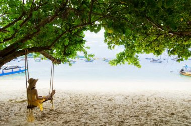 Traveler Asian woman in bikini relaxing on wooden swing and looking at sea, Phi Phi Island, Andaman sea, Krabi, Travel in Thailand, Summer holiday and vacation travel trip.