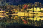 Beautiful autumn with reflections of colorful foliage on the silent lake.
