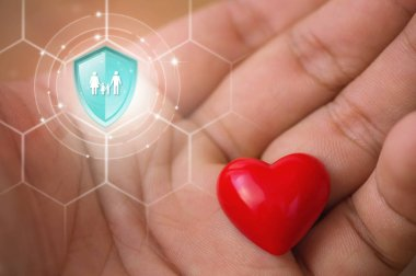Life insurance, Shield protection family on virtual screen against Hearts in hand on backdrop, Concept of insurance, Online insurance digital technology.
