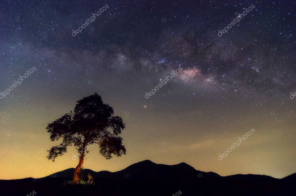 Milky way galaxy with stars and space dust in the universe and Zodiac light on night sky over tree on Mountain landscape with cloud move, Phu Sawan reservoir Phetchaburi.