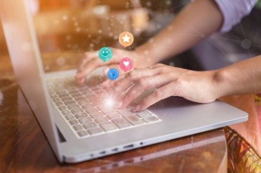 Woman hand pressing on laptop with smiley face, like, love and star emoticons on virtual screen, Customer service evaluation concept.