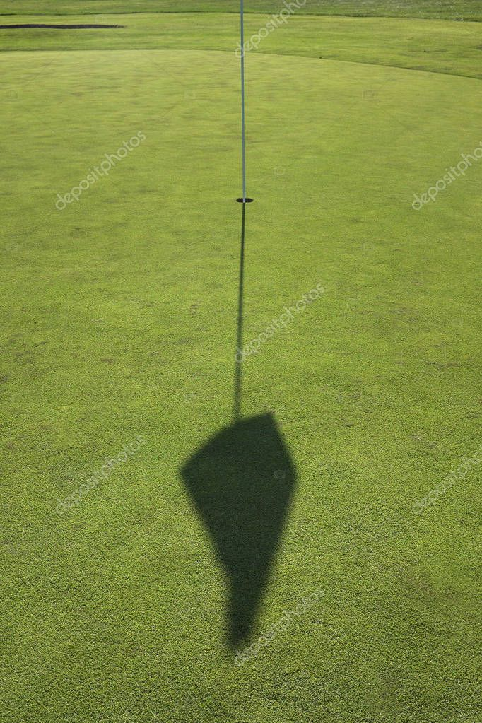The golf course is waiting for players, green grass, a hole, a banner shadow ...