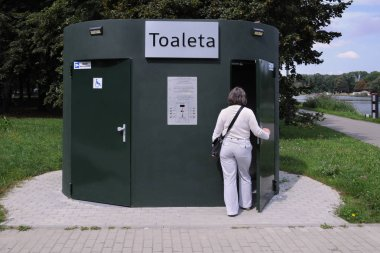 Automatic toilet, public facility in the park, woman enters the previously paid toilet, entrance for disabled on the left ...