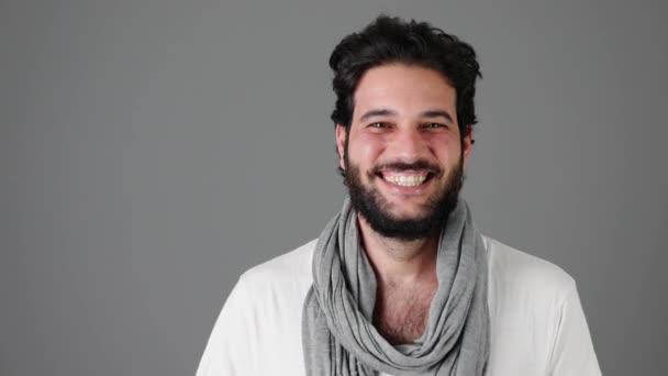 Aufgeregter junger Mann lacht vor grauem Hintergrund