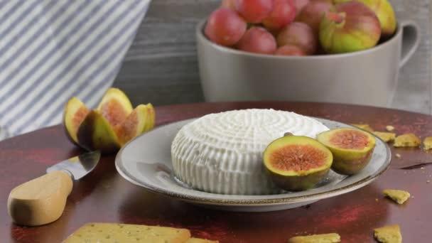 Sýr ricotta s plátky čerstvých fíků na otáčejícím se stole.