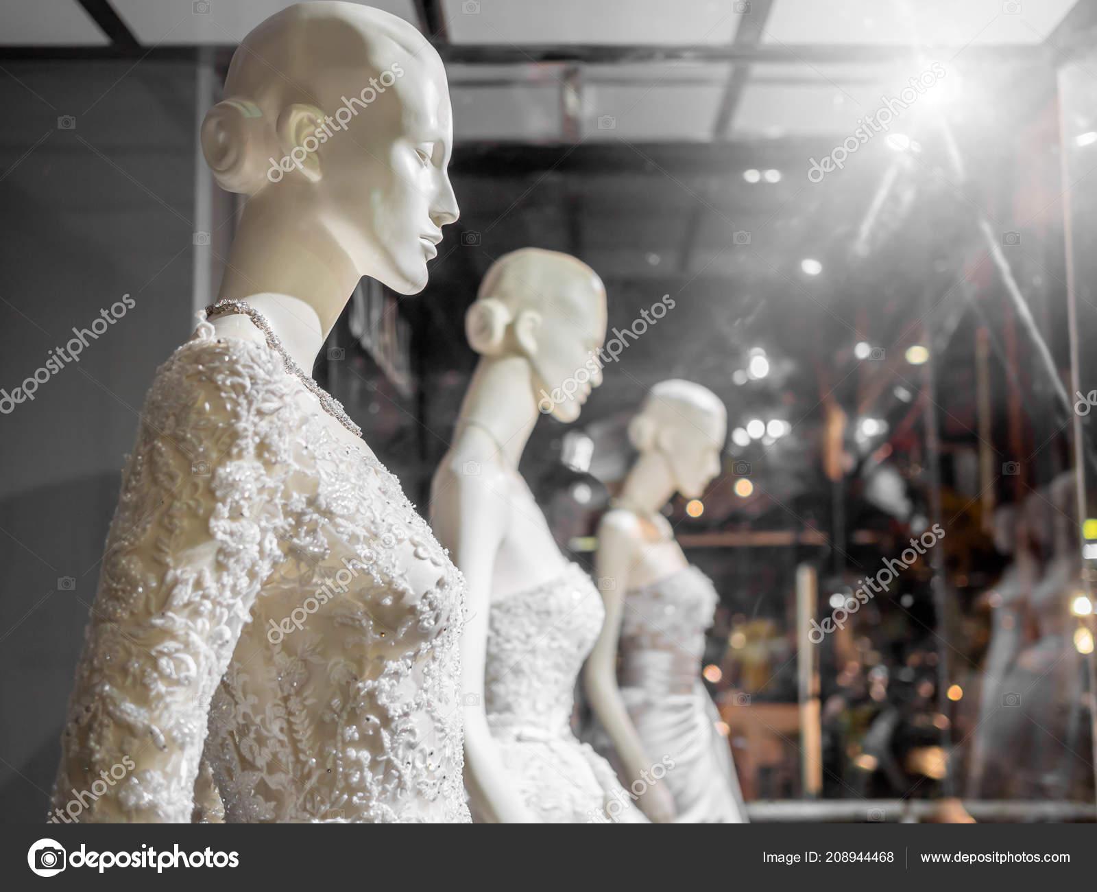 9a080d7136d Maniquí blanco en boda en vitrina. Vestidos de novia en los maniquís en el  escaparate de boda con luz de fondo de tienda de traje de novia — Foto de  ...