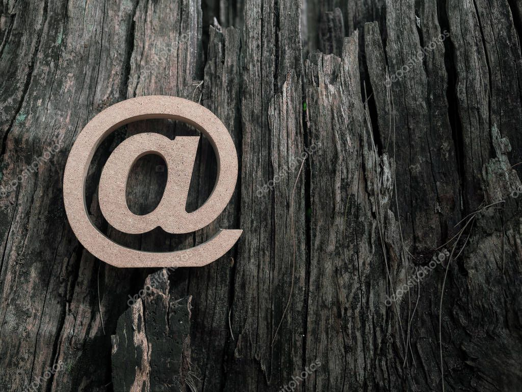 Wooden E-mail address symbol, arroba icon on old dry wooden texture background with copy space. E-mail marketing online internet, technology and environment concept.