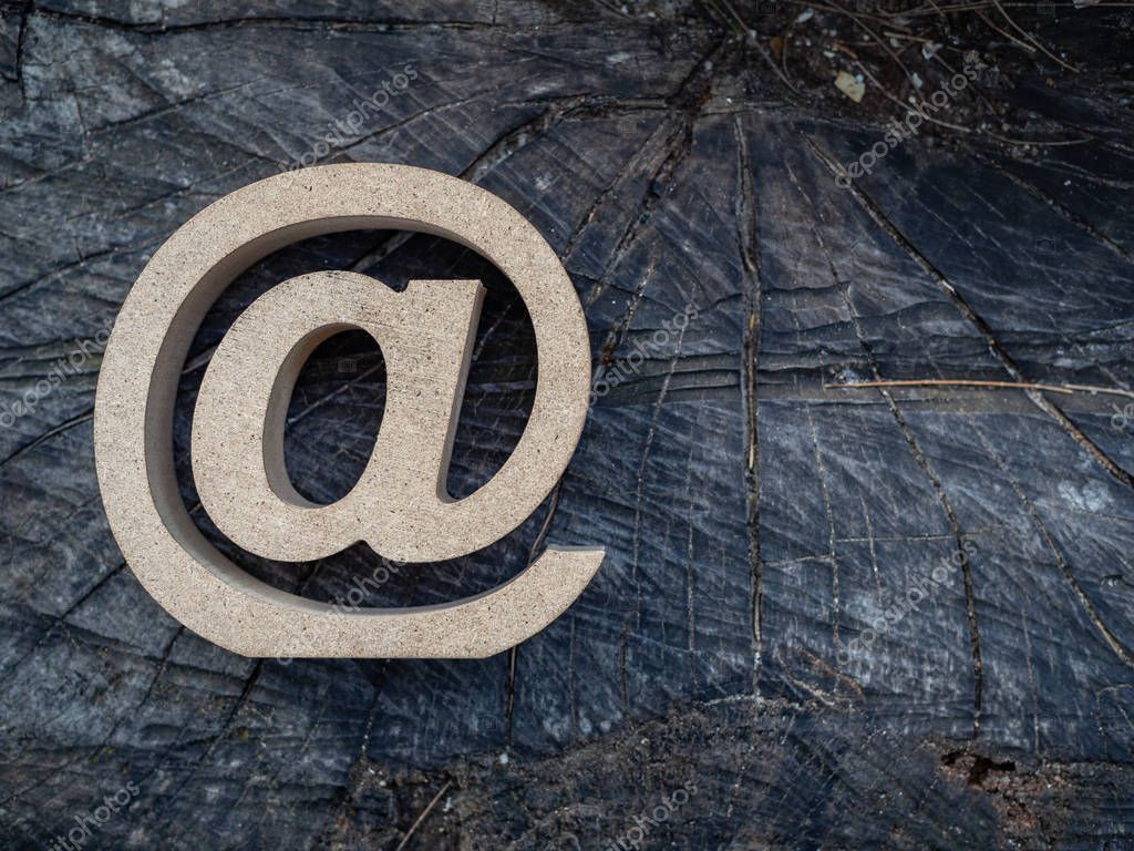 Wooden E-mail address symbol, arroba icon on old dry wooden texture background. E-mail marketing online internet, technology and environment concept.