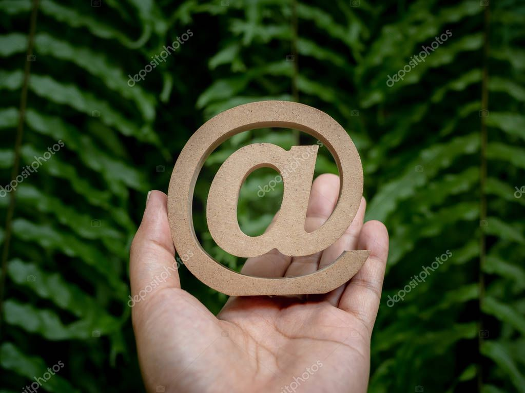 Wooden E-mail address symbol on left hand, arroba icon on green leaves background. E-mail marketing online internet, technology and environment concept.