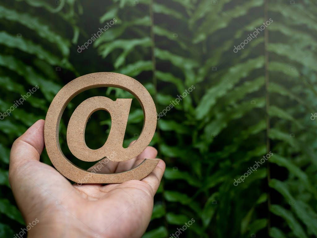 Wooden E-mail address symbol on left hand, arroba icon on green leaves background with copy space. E-mail marketing online internet, technology and environment concept.