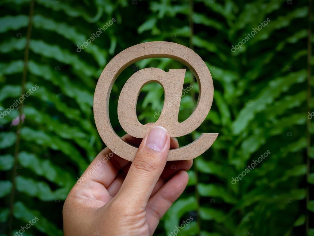 Hand holding wooden E-mail address symbol, arroba icon on green leaves background with copy space. E-mail marketing online internet, technology and environment concept.