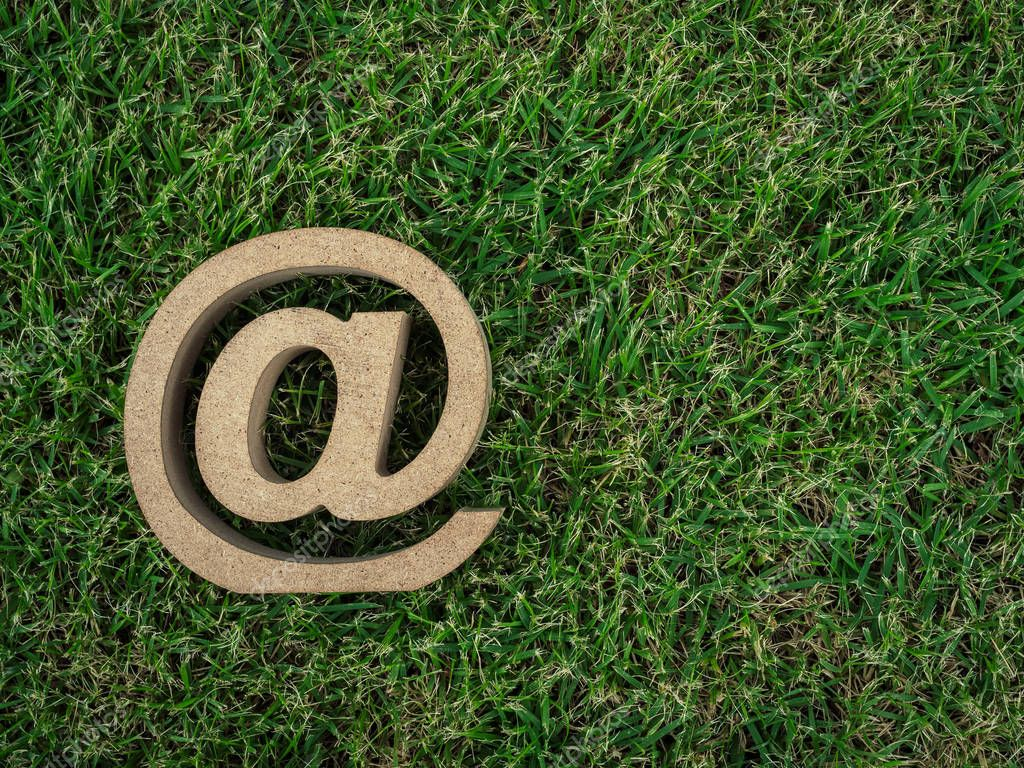 Wooden E-mail address symbol on green grass background with copy space, arroba icon on green leaves background with copy space. E-mail marketing online internet, technology and environment concept.