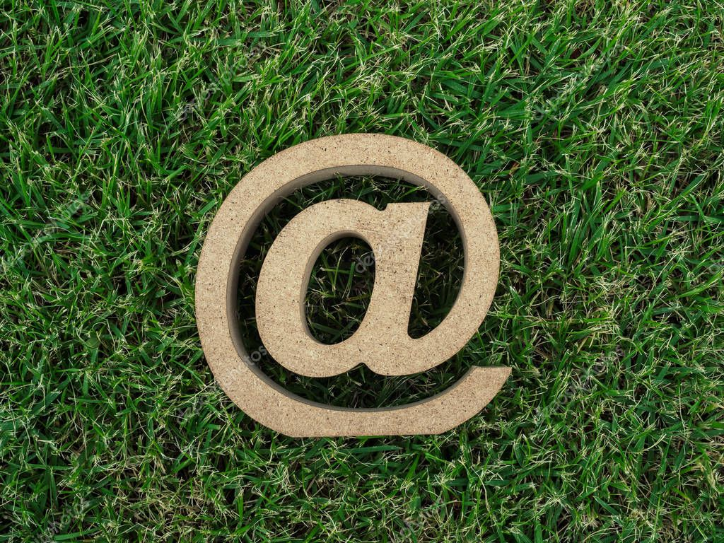 Wooden E-mail address symbol on green grass background, arroba icon on green leaves background with copy space. E-mail marketing online internet, technology and environment concept.
