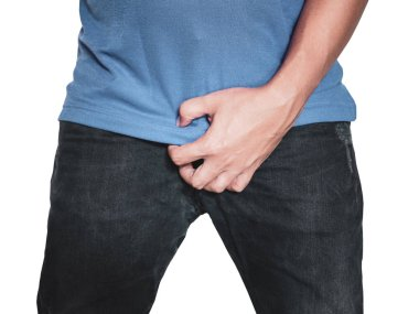 Man hands holding on middle crotch of trousers with pain action isolated on white background.