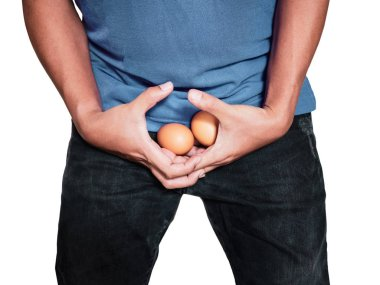 Man hands holding eggs on middle crotch of trousers with pain action isolated on white background.