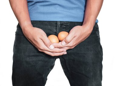 Man hand holding eggs on middle crotch of trousers isolated on white background.