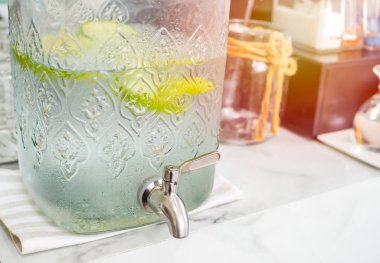 Freshy cold drink water with piece of green apples in cooler bottle on marble counter bar in cafe with copy space.