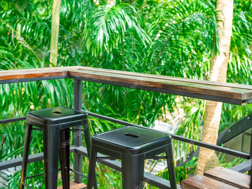 Wooden counter bar and black metal chairs on terrace in the green forest background.