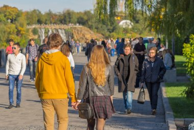 DNEPR, UKRAINE - OCTOBER 02, 2016:Young loving couple walking together on a Dnepr river embankment in center of the Dnepr city at warm and sunny autumnal weeken