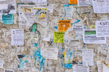Dnepropetrovsk, Ukraine - March 08, 2016:Bulletin board filled with paper notices using mostly for selling apartments