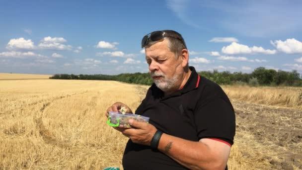 Ukrainian senior farmer eating steamed vegetables sitting outdoor on a harvested wheat field