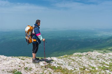 Crimean mountains, Ukraine - May 24, 2013: Hiker admires the scenery of the spring mountains