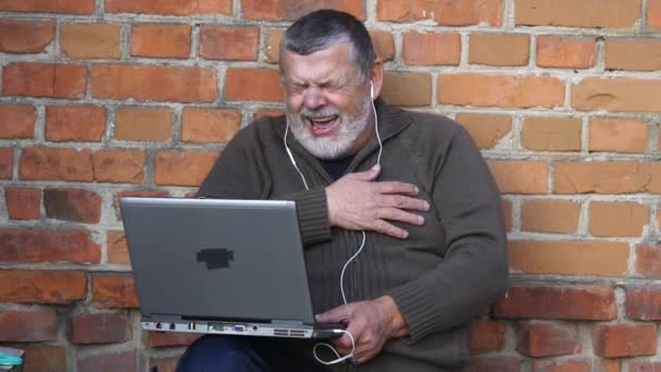 Bearded senior man looking at notebook screen and laughing while sitting outdoor against brick wall
