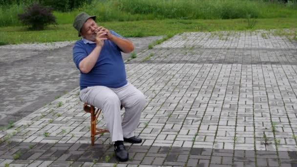 Senior sitzt auf einem Hocker und spielt ukrainisches Holzblasinstrument Sopilka