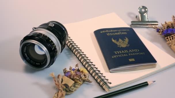 Lapos laikus felvétel-üres könyv, és ceruzával, a tervezési munka vintage objektívvel, Thaiföld hivatalos útlevél és a háttér fehér színű kis virág.