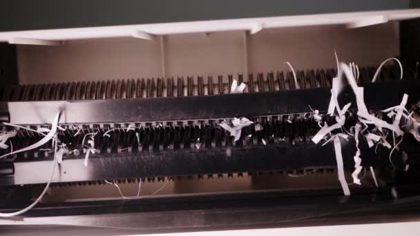 Closeup of the paper shredder that is cutting paper thoroughly for continuous data destruction
