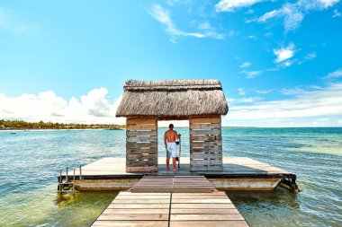 man and woman tourist on jetty in mauritius island, belle mare beach