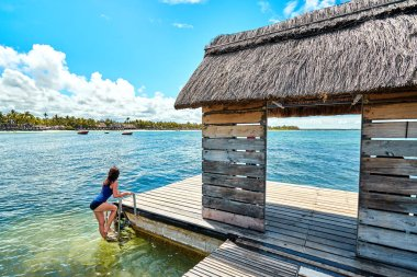 beautiful woman relaxing on jetty beside belle mare beach, mauritius island