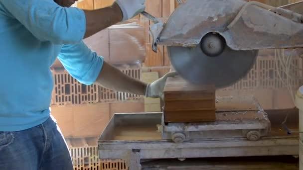 Pracovník pomocí úhlové brusky nebo kotoučovou pilou řezání cihel ve staveniště