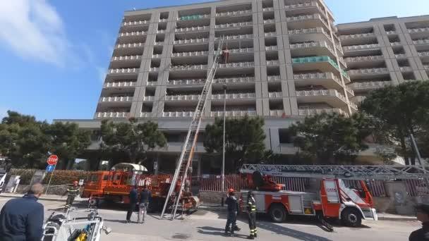 Bari, Itálie – 21. března 2019: hasiči zasahují pro obnovu poškozené vozík elektrický schodiště pro dopravu materiálů a nábytek z bytu mrakodrap