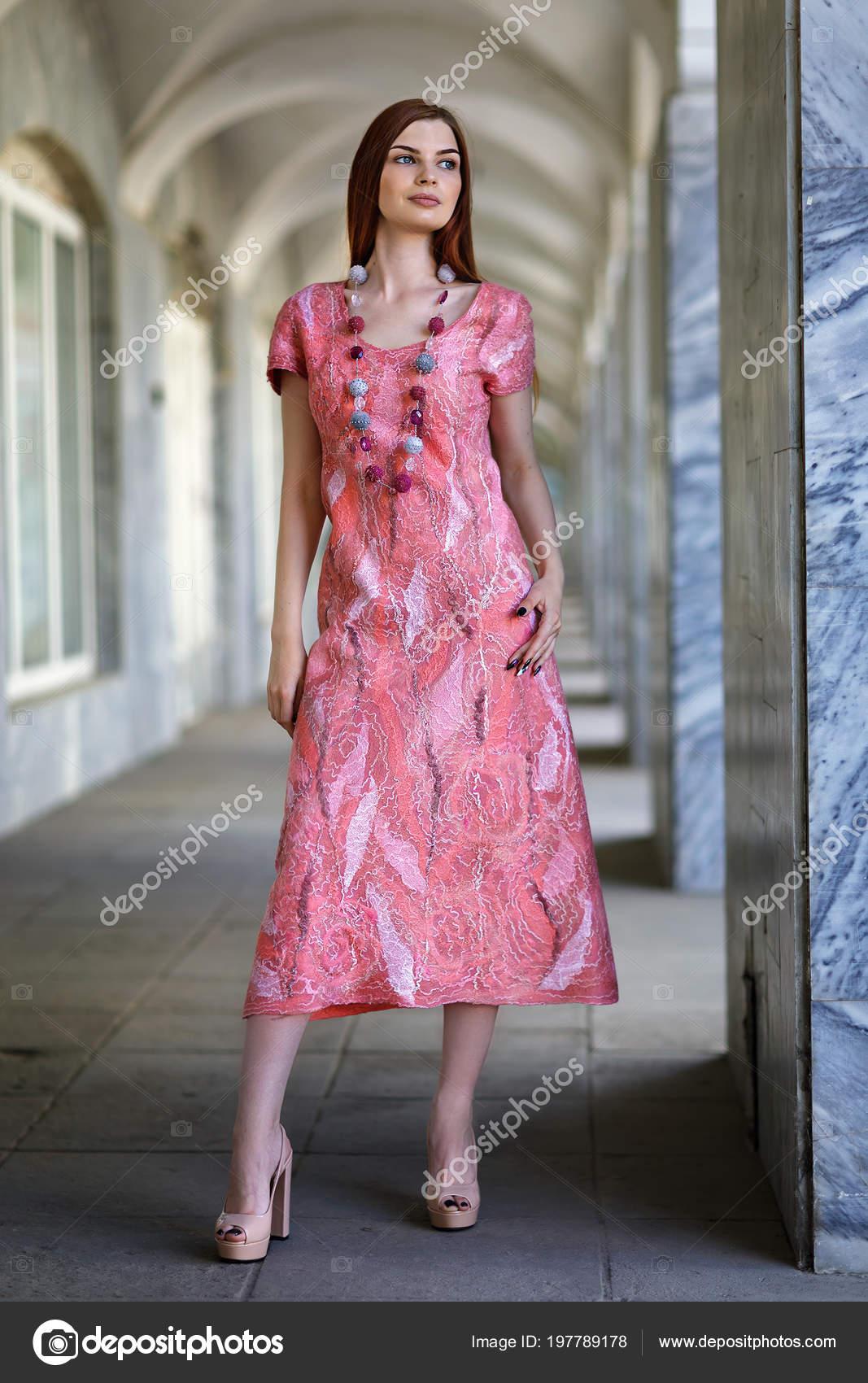 2d2c1af0c050c3 Hermosa jovencita posando en transparente vestido hecho en técnica del  autor de lana merino en la escala de color de rosa-melocotón. Modelo  muestra ropa de ...